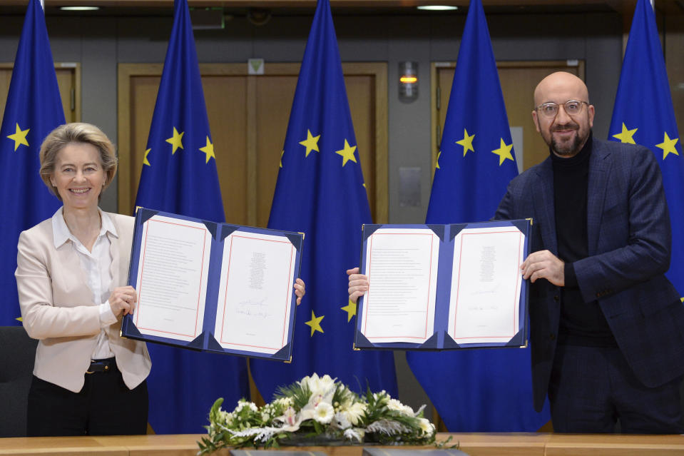 FILE - In this Wednesday, Dec. 30, 2020 file photo, European Commission President Ursula von der Leyen, left, and European Council President Charles Michel show the signed EU-UK Trade and Cooperation Agreement at the European Council headquarters in Brussels. A last-minute trade deal with the United Kingdom coupled with the rollout of COVID-19 vaccines in the final days of the year produced a sense of success for the 27-nation bloc and brought glimmers of hope to the EU's 450 million residents. (Johanna Geron/Pool Photo via AP, File)