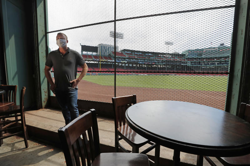 In this June 25, 2020, photo, Joe Hicks, Bleacher Bar director of operations, shows the view of the baseball field at Fenway Park from the bar in Boston. Tucked under the center field seats at Fenway Park, down some stairs from Lansdowne Street in an area previously used as the visiting team's batting cage, is a sports bar that is preparing to reopen from the coronavirus shutdown. If Major League Baseball's plans remain on schedule, it may be one of the few places fans will be able to watch a game in person this season. (AP Photo/Elise Amendola)