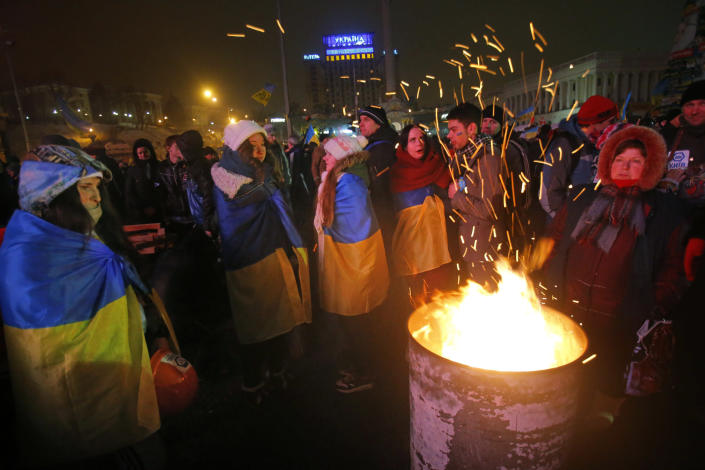 Pro-European Union activists warm themselves near a bonfire during a rally in Independence Square in Kiev, Ukraine, Wednesday, Dec. 11, 2013. Ukraine was thrown into crisis last month when President Viktor Yanukovych suddenly backed away from a long-awaited political and economic agreement with the European Union, deciding to focus instead on restoring trade ties with Russia. (AP Photo/Sergei Grits)