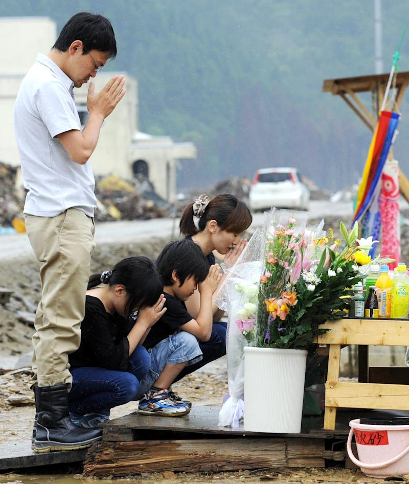 Bereaved family members pray for the victims of the March 11 earthquake and tsunami at Okawa elementary school, where 74 of the 108 students died in the disasters, in Ishinomaki, Miyagi prefecture, Saturday, June 11,2011.  Japan marked three month since the disasters killed tens of thousands and caused one of the world's worst nuclear crisis, on Saturday. (AP Photo/Kyodo News) JAPAN OUT, MANDATORY CREDIT, NO LICENSING IN CHINA, HONG KONG, JAPAN, SOUTH KOREA AND FRANCE