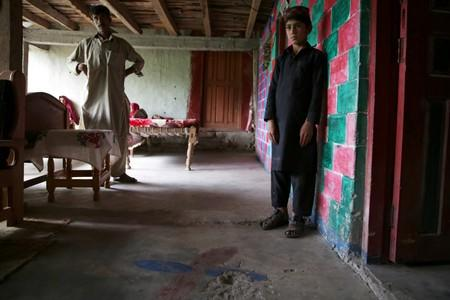 Raja Nauman, 10, stands next to a crater on the floor of his house, caused by a cluster bomb that according to family looked like a toy and exploded in the hands of a child, in village Jabri, in Neelum Valley