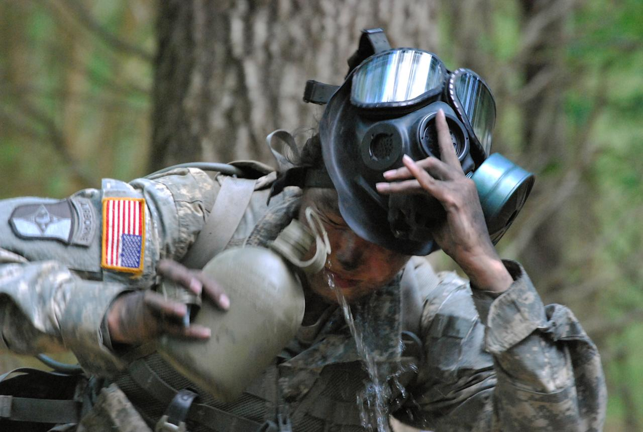 In a May 9, 2012 photo, Capt. Sara Rodriguez of the 101st Airborne Division pours water on her face during the expert field medical badge testing at Fort Campbell, Ky., Female soldiers are moving into new jobs in once all-male units as the U.S. Army breaks down formal barriers in recognition of what's already happened in wars in Iraq and Afghanistan. (AP Photo/Kristin M. Hall)