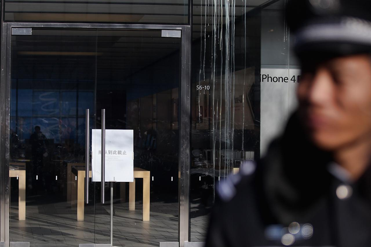 BEIJING, CHINA - JANUARY 13:  A policeman guards outside the Apple store beside the egg's stains on its glass wall on January 13, 2012 in Beijing, China. Chinese angry crowd shouted and threw eggs outside Apple's Beijing flagship store after it failed to open on schedule Friday to sell iPhone 4S.  (Photo by Feng Li/Getty Images)