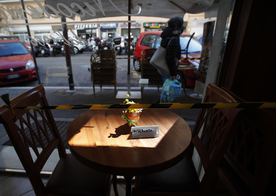 A plastic tape prevents people from sitting at a coffee table in downtown Rome, Monday, March 15, 2021. Half of Italy's regions have gone into the strictest form of lockdown in a bid to curb the latest spike in coronavirus infections that have brought COVID-19 hospital admissions beyond manageable thresholds.(AP Photo/Alessandra Tarantino)