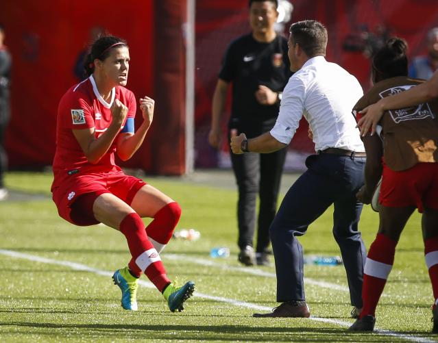 Canada's Christine Sinclair celebrates her game-winning stoppage-time penalty shot goal against China with head coach John Herdman against China during a FIFA Women's World Cup soccer match in Edmonton, Alberta, Saturday, June 6, 2015. (Jeff McIntosh/The Canadian Press via AP) MANDATORY CREDIT
