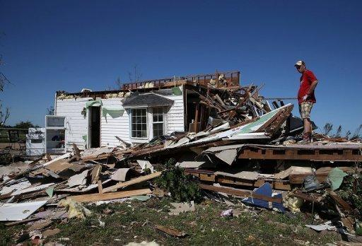 A man sifts looks at his damaged home after a series of tornadoes June 1, 2013 in El Reno, Oklahoma. Three veteran storm chasers were killed while pursuing powerful tornadoes that tore through the US state of Oklahoma, a relative said