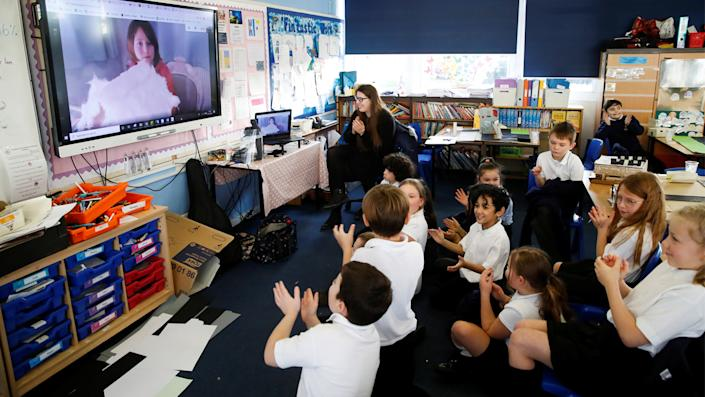 Students at Holne Chase School interact with a class member via the internet as his family is self-isolating amid the Coronavirus disease (Covid-19) in Milton Keynes, Britain, December 1, 2020. (Andrew Boyers/Reuters)