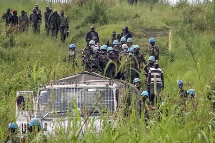 United Nations peacekeepers remove bodies from an area near to where a U.N. convoy was attacked and the Italian ambassador to Congo killed, in Nyiragongo, North Kivu province, Congo Monday, Feb. 22, 2021. The Italian ambassador to Congo Luca Attanasio, an Italian Carabineri police officer and their Congolese driver were killed Monday in an attack on a U.N. convoy in an area that is home to myriad rebel groups, the Foreign Ministry and local people said. (AP Photo/Justin Kabumba)