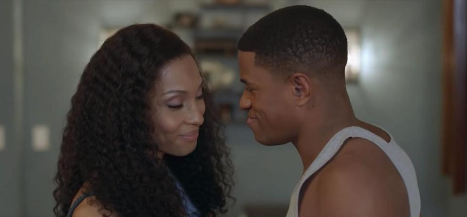 a woman stands face to face with a man and grins with her eyes closed