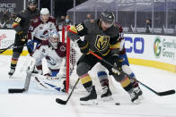 Vegas Golden Knights left wing William Carrier (28) skates around Colorado Avalanche defenseman Jacob MacDonald (26) during the second period of an NHL hockey game Monday, May 10, 2021, in Las Vegas. (AP Photo/John Locher)