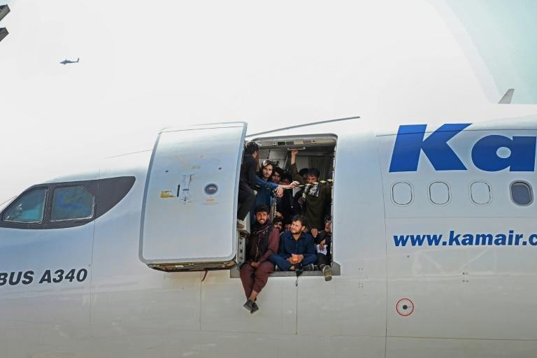 Afghan people climb up on a plane and sit by the door as they wait at Kabul's airport