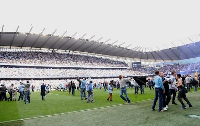 Manchester City's supporters celebrate on the pitch after their team's 3-2 victory over Queens Park Rangers in the English Premier League football match between Manchester City and Queens Park Rangers at The Etihad stadium in Manchester, north-west England on May 13, 2012. Manchester City won the game 3-2 to secure their first title since 1968. This is the first time that the Premier league title has been decided on goal-difference, Manchester City and Manchester United both finishing on 89 points. AFP PHOTO/PAUL ELLIS RESTRICTED TO EDITORIAL USE. No use with unauthorized audio, video, data, fixture lists, club/league logos or 'live' services. Online in-match use limited to 45 images, no video emulation. No use in betting, games or single club/league/player publications.PAUL ELLIS/AFP/GettyImages