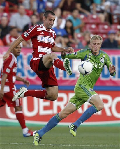 FC Dallas's Andrew Jacobson leaps to pass the ball in front of Seattle Sounders' Andy Rose, rear, during the first half of an MLS soccer game, Wednesday, May 9, 2012, in Frisco, Texas. (AP Photo/Tony Gutierrez)