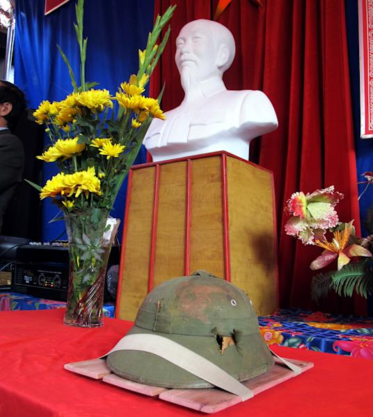 A dented helmet belonging to Bui Duc Hung, a slain North Vietnamese soldier who died during the Vietnam War, is displayed in front of a bust of late Vietnamese revolutionary leader Ho Chi Minh in Huong Non village, northern Phu Tho province, Vietnam on Tuesday, Jan. 14, 2014. The helmet, which had been kept as a war souvenir by an American veteran for 46 years, was returned to the extended family of Bui Duc Hung. (AP Photo/Tran Van Minh.)