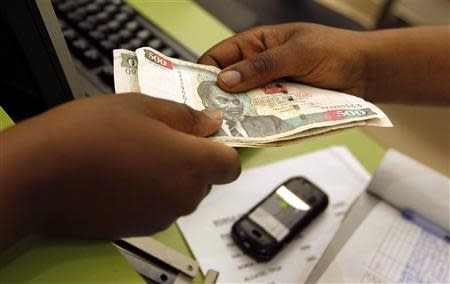 A customer conducts a mobile money transfer, known as M-Pesa, inside the Safaricom mobile phone care centre in the central business district of Kenya's capital Nairobi in this July 15, 2013 file photo. REUTERS/Thomas Mukoya/Files