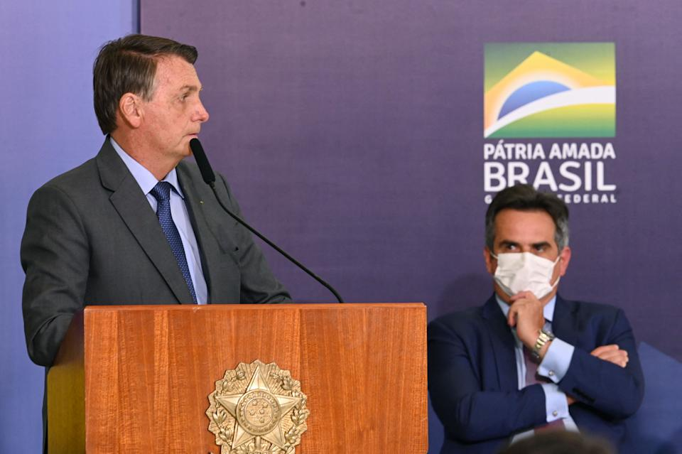Brazilian President Jair Bolsonaro (L) speaks while senator Ciro Nogueira observes, during a press conference to launch the Public Integrity System, aimed to combat corruption in the fedetal government, at the Planalto Palace in Brasilia, on July 27, 2021. - Nogueira was appointed by Bolsonaro as the new Chief of Staff. (Photo by EVARISTO SA / AFP) (Photo by EVARISTO SA/AFP via Getty Images)