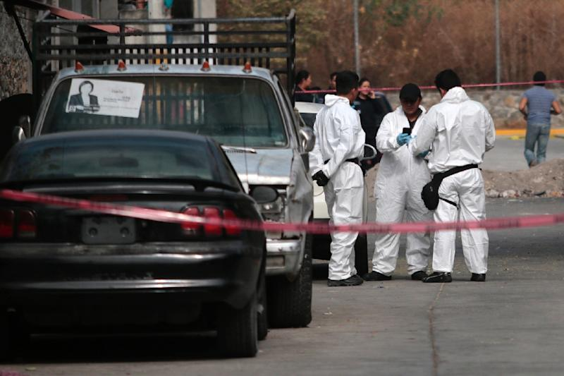 Forensic personnel stand by on January 2, 2016 outside the house of Gisela Mota, murdered at her home by gunmen