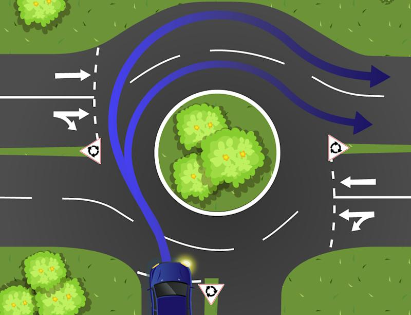 A blue car is pictured entering a two lane roundabout.
