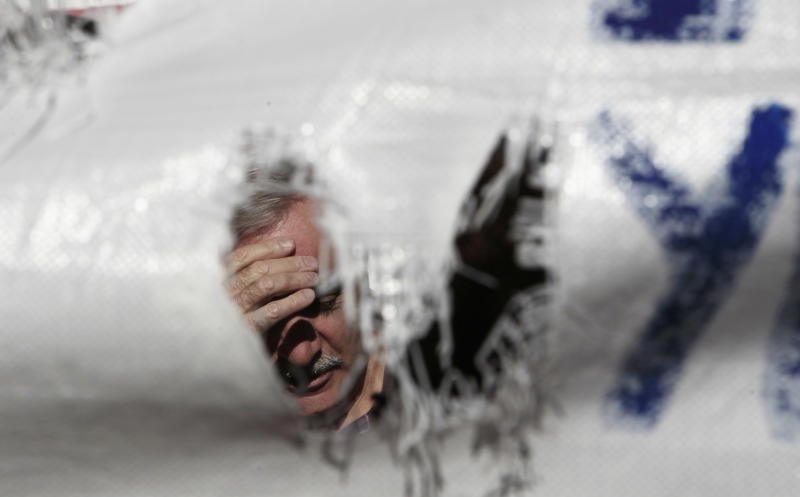 A protester holds his head behind a banner during a protest outside Health Ministry in Athens, Friday, Nov. 29, 2013. Greek state hospitals are functioning with emergency staff as doctors and staff hold a 24-hour strike against planned health cutbacks enforced under the country's harsh austerity program. Unions are angry at the conservative-led government's plans to suspend and reallocate staff as part of its drive to reform the public sector and reduce the budget deficit. (AP Photo/Thanassis Stavrakis)