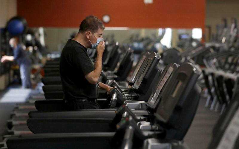 A man in the US working out on a treadmill, while wearing a mask - AP