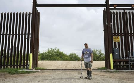Fernando Rivera Jr. poses at the open gate of the 18-foot (five-metre) high rusty steel barrier along the U.S.-Mexico border outside Brownsville, Texas September 2, 2014. REUTERS/Rick Wilking