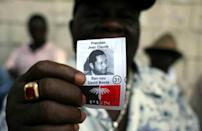 """A former member of Tonton Macoute paramilitary force displays a photograph of Jean-Claude """"Baby Doc"""" Duvalier while on guard outside a private hospital in Port-au-Prince where the ex-dictator was being treated in 2011"""