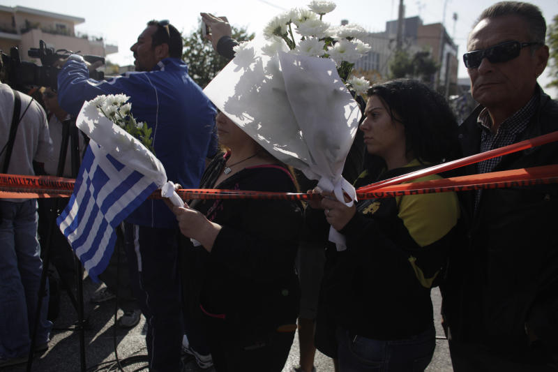 Supporters of the extreme right party Golden Dawn hold flowers and a Greek national flag in front of the party's office in northern Athens, Saturday, Nov. 2, 2013. Police looking for clues to the Friday evening murder of two members of the far-right Golden Dawn party and the grievous injury to a third say the gun used in the attack has not been used in previous terrorist attacks. (AP Photo/Kostas Tsironis)