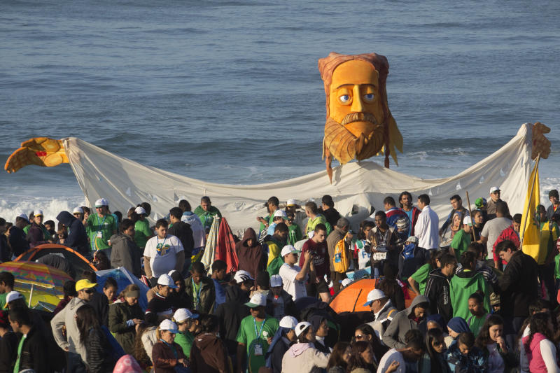 Pilgrims carry a large puppet representing Jesus as they wait for Pope Francis' arrival on Copacabana beach in Rio de Janeiro, Brazil, Sunday, July 28, 2013. Hundreds of thousands of young people slept under chilly skies in the white sand awaiting Pope Francis' final Mass for World Youth Day.(AP Photo/Victor R. Caivano)