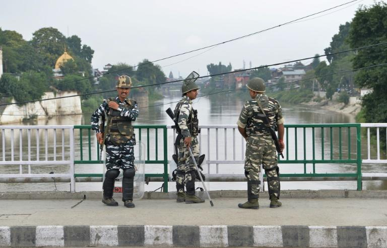 Indian security personnel stand guard on a bridge in Srinagar
