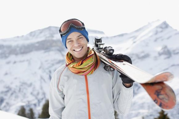 A smiling man holding snow skis.