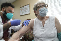 Betty Lou Wahlstedt, 88, right, receives the COVID-19 vaccination from pharmacist Jeffery Smith at a senior living residents facility Monday, Jan. 11, 2021, in Plano, Texas. The U.S. is entering the second month of the biggest vaccination effort in history with a major expansion of the campaign. (AP Photo/LM Otero)