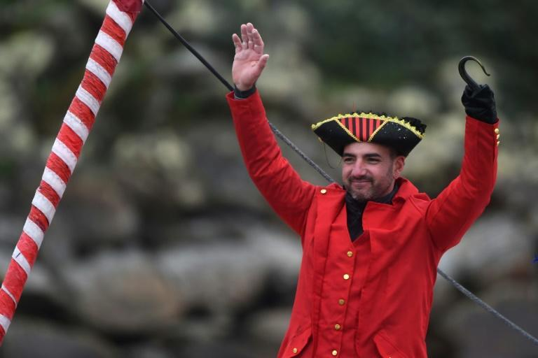 French skipper Damien Seguin, disguised as a pirate, celebrates after crossing the finish line in sixth position