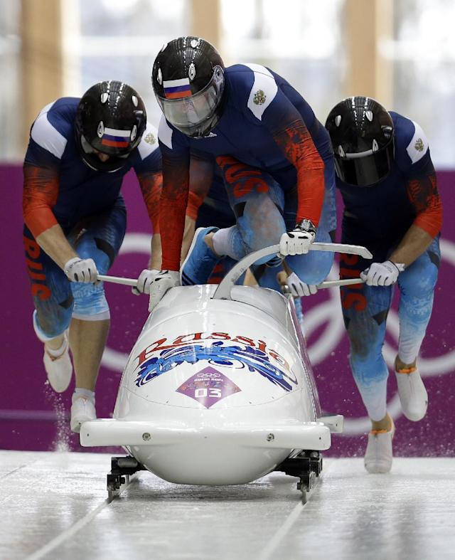 The team from Russia RUS-1, with Alexander Zubkov, Alexey Negodaylo, Dmitry Trunenkov, and Alexey Voevoda, start their third run during the men's four-man bobsled competition final at the 2014 Winter Olympics, Sunday, Feb. 23, 2014, in Krasnaya Polyana, Russia. (AP Photo/Natacha Pisarenko)
