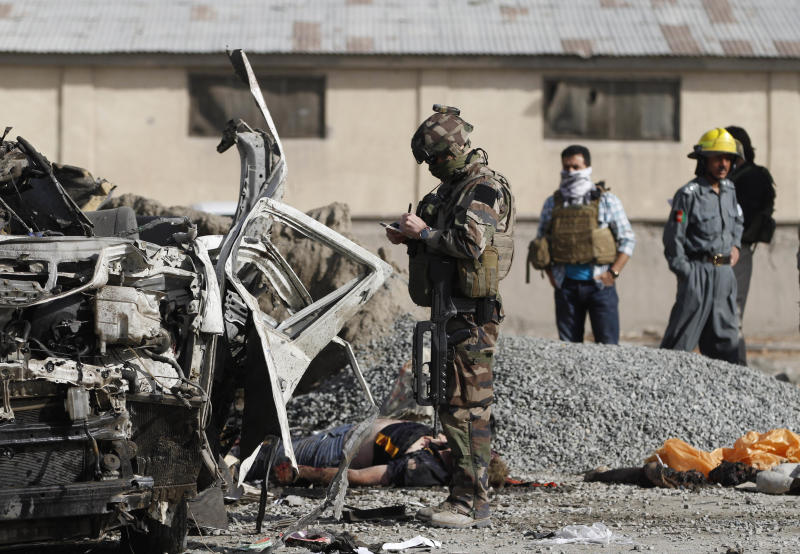 A French soldier investigates the scene of a suicide bombing in Kabul, Afghanistan, Tuesday, Sept. 18, 2012. A suicide bomber rammed a car packed with explosives into a mini-bus carrying foreign aviation workers to the airport in the Afghan capital early Tuesday, killing at least nine people in an attack a militant group said was revenge for an anti-Islam film that ridicules the Prophet Muhammad. (AP Photo/Ahmad Jamshid)