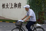 A man bicycles past an Evergrande new housing development in Beijing, Wednesday, Sept. 15, 2021. One of China's biggest real estate developers is struggling to avoid defaulting on billions of dollars of debt, prompting concern about the broader economic impact and protests by apartment buyers about delays in completing projects. Rating agencies say Evergrande Group appears likely to be unable to repay all of the 572 billion yuan ($89 billion) it owes banks and other bondholders. That might jolt financial markets, but analysts say Beijing is likely to step in to prevent wider damage. (AP Photo/Andy Wong)