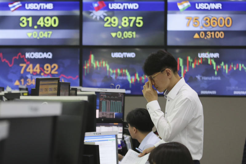 A currency trader watches monitors at the foreign exchange dealing room of the KEB Hana Bank headquarters in Seoul, South Korea, Wednesday, June 3, 2020. Asian shares are rising after Wall Street extended its gains for the third straight day, driven by optimism over economies reopening from shutdowns to stem the coronavirus pandemic. (AP Photo/Ahn Young-joon)