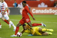 FILE - In this Oct. 15, 2019, file photo, U.S. goalkeeper Zack Steffen, bottom, watches as Canada forward Jonathan David (20) lines up a shot on net during the first half of a CONCACAF Nations League soccer match in Toronto. Steffen figures to make a rare appearance in goal Thursday, Nov. 12, when the United States plays Wales in Swansea. The 25-year-old is the top American goalkeeper but has played two matches since December, missing the second half of last season with a knee injury while on loan to Fortuna Düsseldorf and then spending most of this season on Manchester City's bench after taking over from Claudio Bravo as Ederson's backup. (Cole Burston/The Canadian Press via AP, File)