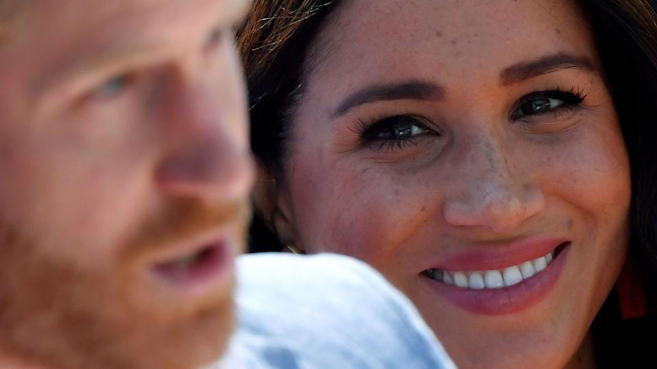 Meghan, Duchess of Sussex, looks on as Prince Harry, Duke of Sussex, gives a speech