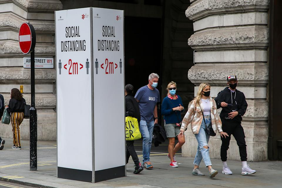 """LONDON, UNITED KINGDOM - 2020/08/31: Members of public wearing face masks walk past a """"Social Distancing"""" sign at Regents Street during coronavirus pandemic. It is mandatory to wear face masks while travelling. (Photo by Dinendra Haria/SOPA Images/LightRocket via Getty Images)"""