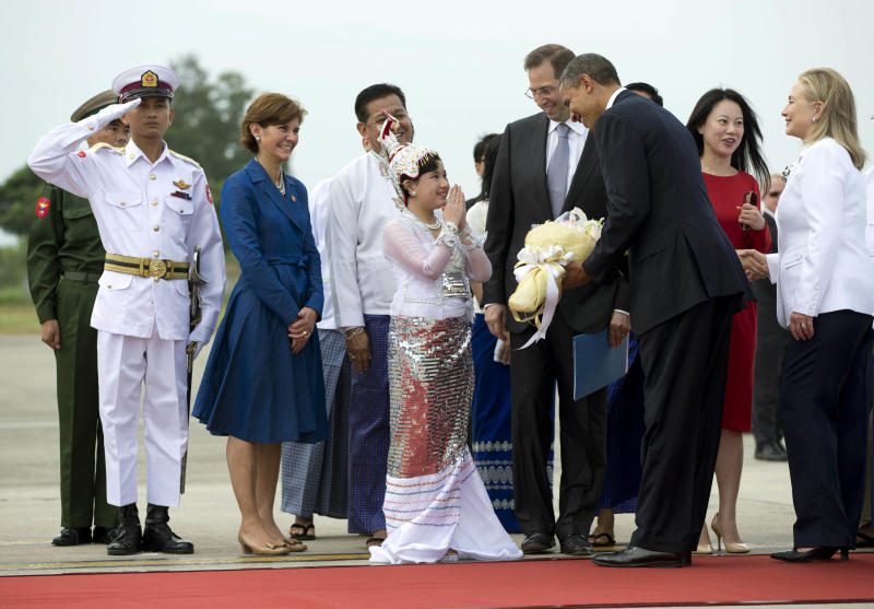 U.S. President Barack Obama is presented with flowers as he and Secretary of State Hillary Rodham Clinton, right, arrive at Yangon International Airport in Yangon, Myanmar, on Air Force One, Monday, Nov. 19, 2012. This is the first visit to Myanmar by a sitting U.S. president. (AP Photo/Carolyn Kaster)