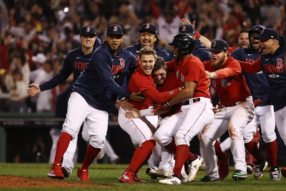 The Red Sox celebrate at home plate after walking off with a Game 4 win to eliminate the Rays and advance to the ALCS.