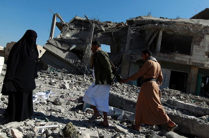Yemenis walk past the site of a Saudi-led airstrike that targeted a building in the Yemeni capital Sanaa on January 25, 2016 (AFP Photo/Mohammed Huwais )