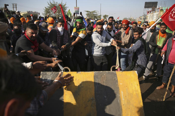 Protesting farmers remove a concrete barricade set up by policemen, as they attempt to move towards Delhi, at the border between Delhi and Haryana state, Friday, Nov. 27, 2020. Thousands of agitating farmers in India faced tear gas and baton charge from police on Friday after they resumed their march to the capital against new farming laws that they fear will give more power to corporations and reduce their earnings. While trying to march towards New Delhi, the farmers, using their tractors, cleared concrete blockades, walls of shipping containers and horizontally parked trucks after police had set them up as barricades and dug trenches on highways to block roads leading to the capital. (AP Photo/Altaf Qadri)