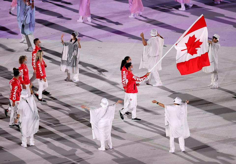 <p>TOKYO, JAPAN - JULY 23: Flag bearers Miranda Ayim and Nathan Hirayama of Team Canada lead their team in during the Opening Ceremony of the Tokyo 2020 Olympic Games at Olympic Stadium on July 23, 2021 in Tokyo, Japan. (Photo by Cameron Spencer/Getty Images)</p>