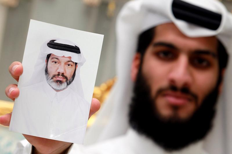 In this Sunday Sept. 8, 2013 photo, Hasan al-Jaidah holds a photograph of his father, detained Qatari doctor Mahmoud al-Jaidah, at the family's home in Doha, Qatar. More than six months ago, Dr. al-Jaidah was asked to step out of line as he transited through Dubai en route home to Qatar. He has been held ever since, allowed to visit his family once a month after a blindfolded trip from an undisclosed detention facility. UAE authorities have given no public statements on the case. But the family of the 52-year-old doctor has no doubt why he was detained: He has been caught up in the escalating pressures across the Western-backed Gulf states against the now-battered Muslim Brotherhood and its perceived Islamist allies. (AP Photo/Osama Faisal)