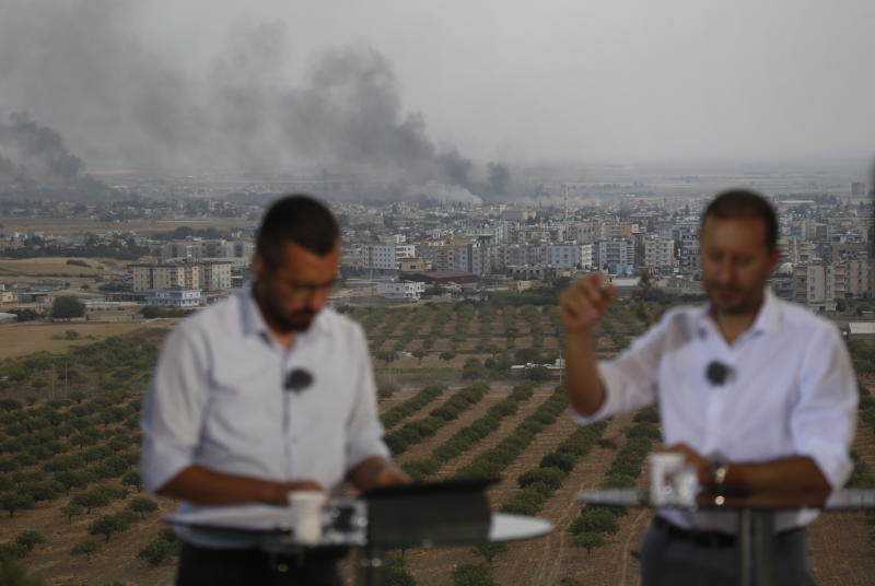 TV journalists talk during a live broadcast on a hilltop in Ceylanpinar, Sanliurfa province, southeastern Turkey, as in the background smoke billows from targets in Ras al-Ayn, Syria, during bombardment by Turkish forces, Oct. 16, 2019. (Photo: Lefteris Pitarakis/AP)