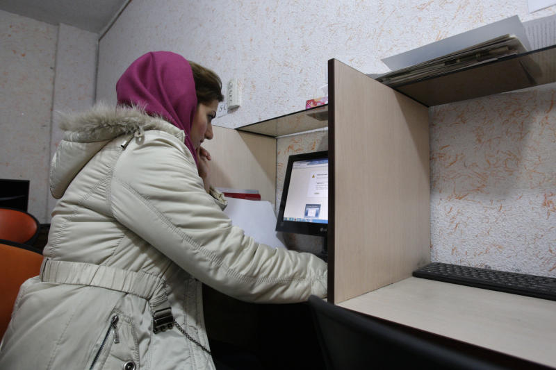 """In this picture taken on Monday, Feb. 13, 2012, an Iranian woman uses a computer in an internet cafe in central Tehran, Iran. Iran calls it the """"soft war"""" with the West: Battles to control, defend and monitor the web and telecommunications. The latest move came from the Revolutionary Guard, launching what they claim is a hack-proof phone network for high-level commanders. Tehran's efforts to build a cyber-fortress have become a priority among leaders fearful of Internet espionage and virus attacks from abroad and seeking to choke off opposition voices at home. (AP Photo/Vahid Salemi)"""
