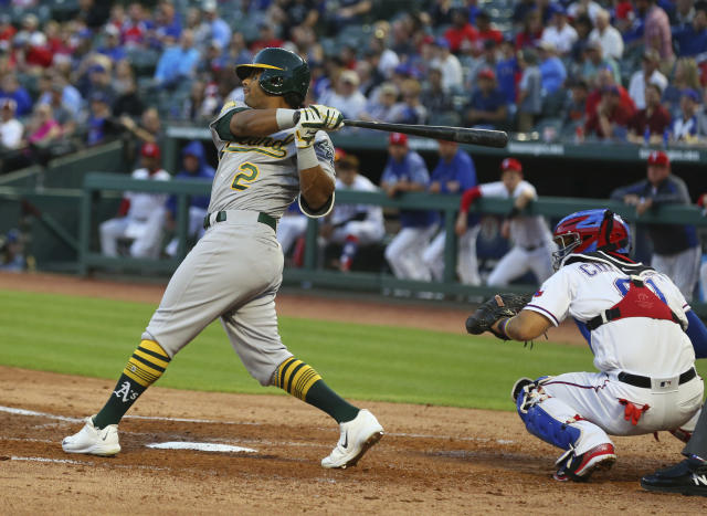 Oakland Athletics designated hitter Khris Davis (2) hits a two-run double in the third inning of a baseball game against the Texas Rangers Monday, April 23, 2018, in Arlington, Texas. (AP Photo/Richard W. Rodriguez)