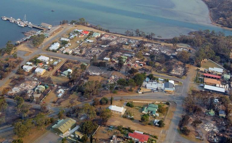 This aerial photograph taken on January 5, 2013 shows the devastated town of Dunalley after bush fires swept through the area.  Thousands of people have fled wildfires raging on the Australian island of Tasmania that have destroyed at least 80 properties amid fears that at least one man died in the blaze, police said.  AFP PHOTO / POOL / Chris Kidd