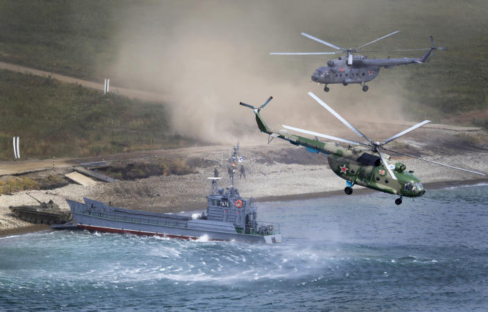 """A Russian navy landing vessel unloads an armored vehicle as military helicopters fly overhead during Russian military maneuvers Vostok 2018 on the training ground """"Klerk,"""" about 50 kilometers (31 miles) south of Vladivostok, Russian Far East port, Russia, Saturday, Sept. 15, 2018. The weeklong Vostok 2018 maneuvers are the largest war games Russia ever had. (AP Photo/Sergei Grits)"""